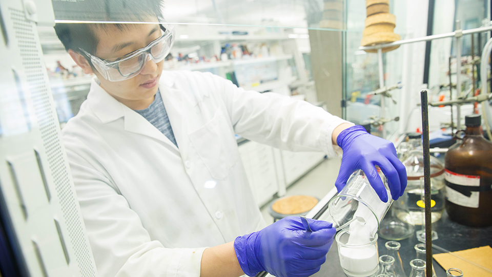 Man working in a lab, wearing gloves, goggles and a lab coat